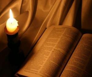 puzzel De Bijbel en een brandende kaarsen op het altaar