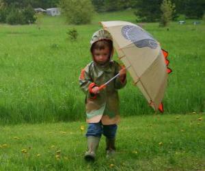 puzzel Jongen met zijn paraplu en regenjas onder de lenteregen