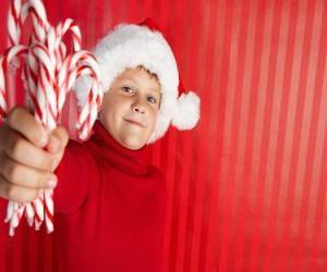 puzzel Kind met hoed van de kerstman en snoep stokken in de hand