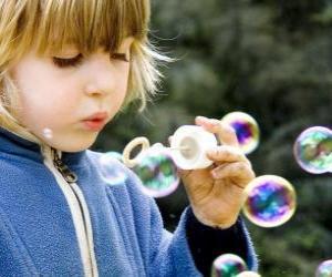 puzzel Kind speelt om zeepbellen blazen