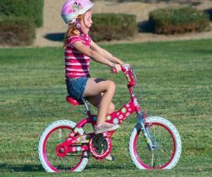 puzzel Meisje rijdt op een fiets in het park in het voorjaar