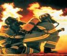Brandbestrijder met een knie op de vloer en slang klaar