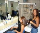 Kapper kammen en drogen van het haar aan een klant in de beautysalon of de kapper