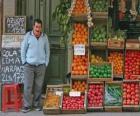 De verkoper van groenten en fruit in zijn winkel