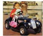 Meisje op een klassieke speelgoed auto