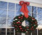Groot kerstkrans versierd met een groot lint en ballen