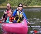 Familie, vader, moeder en dochter, zeilen en een kano peddelen, uitgerust met zwemvesten