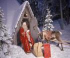 Santa aan de deur van zijn huis met een rendier en cadeaus