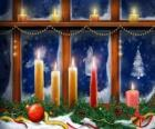 Kerst kaarsen aangestoken in de voorkant van een raam