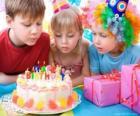 Meisje in het moment van uitblazen van de kaarsjes op haar verjaardagstaart