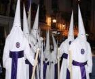Christenen of boetelingen in een optocht tijdens de Goede Week met capuchon of kegel, badjas en cape