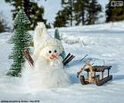 Een kleine sneeuwpop naast zijn slee
