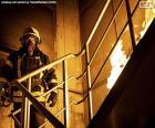 Brandweerman op een brandende ladder