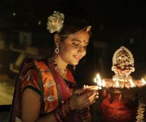 puzzel Vrouw geknield met een olielamp in haar hand in de viering van Divali